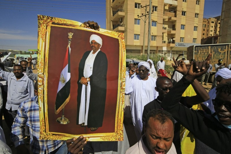 Supporters of Sudan's ousted president Omar Al-Bashir rally in front of a court in the capital Khartoum during the former leader's trial on Saturday. -AFP