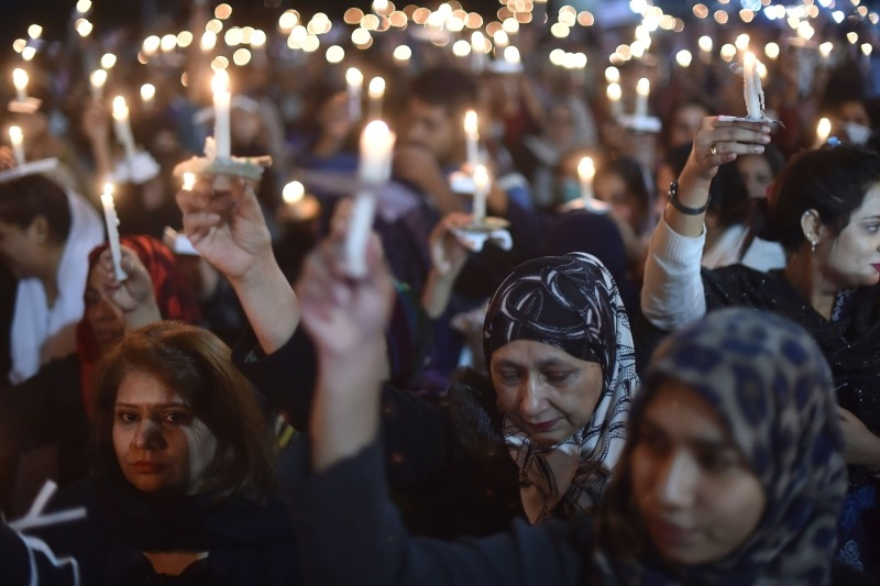 Paramedic staff members participate in a candle light vigil for the victims who lost their lives during an attack by a group of lawyers on Punjab Institute of Cardiology (PIC), in Lahore on Friday. At least three heart patients died on Dec. 11 after a group of lawyers attacked doctors at a cardiac hospital in Pakistan's eastern city of Lahore, officials and ministers said. — AFP