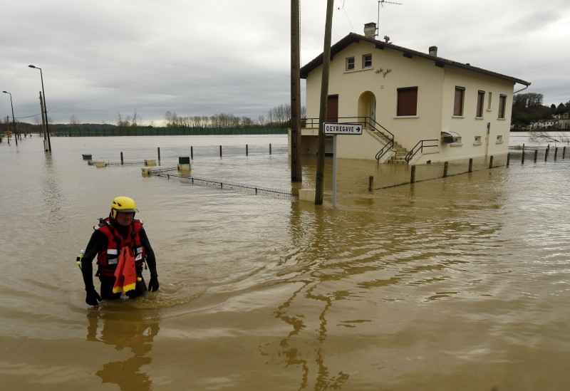 A firefighter walks in a flooded neighborhood following heavy rains in Peyrehorade, southwestern France, on Saturday. About 70,000 houses were cut from electricity on Friday in southwestern France after heavy rains and violent winds. One person died and five others were injured as the floods threaten the Pyrenees-Atlantiques region. — AFP