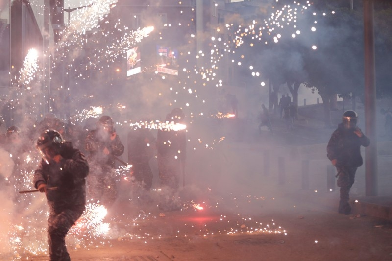 Lebanese riot police react to fireworks thrown by supporters of Lebanon's Shiite Hezbollah and Amal groups during clashes on Saturday in central Beirut. — AFP
