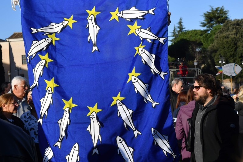 A demonstrator holds a European Flag on which he has fixed paper cutouts of sardines, during a demonstration of the