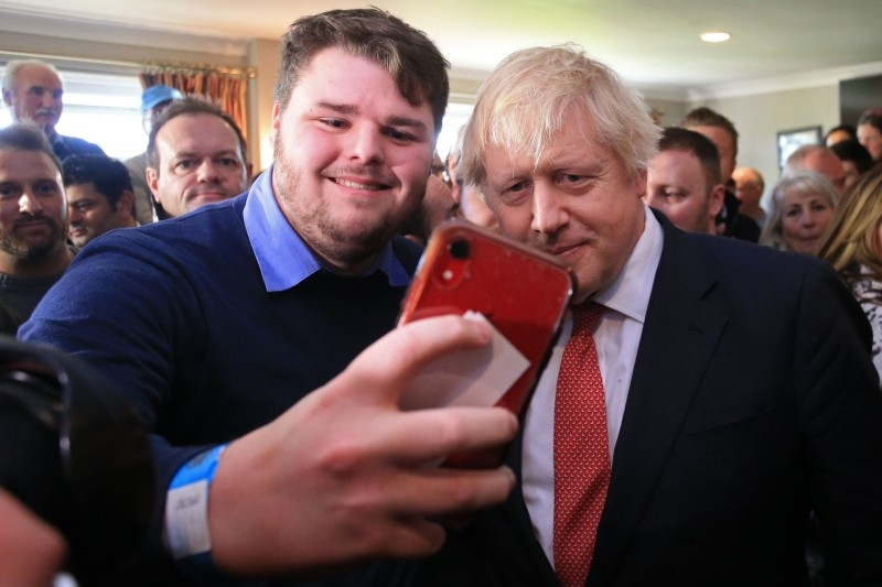 Britain's Prime Minister Boris Johnson has a selfie photograph taken with a supporter during a visit to see newly elected Conservative party MP for Sedgefield, Paul Howell at Sedgefield Cricket Club in County Durham, northeast England  on Saturday. -AFP