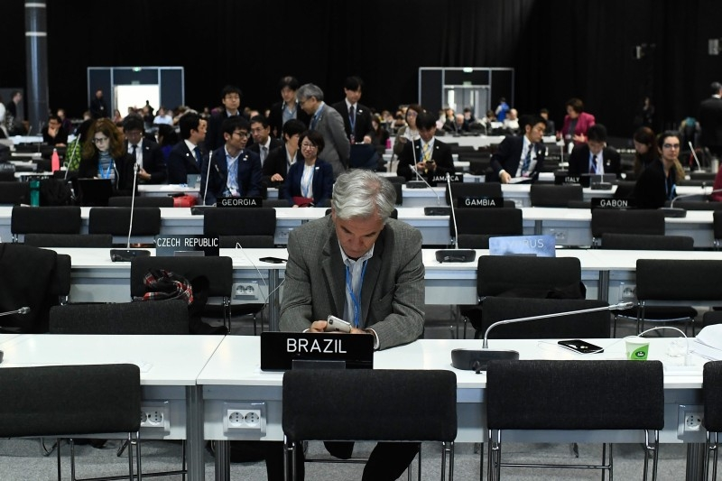 Delegates wait for the start of the closing plenary session of the UN Climate Change Conference COP25 at the 'IFEMA - Feria de Madrid' exhibition centre, in Madrid, on Sunday. -AFP