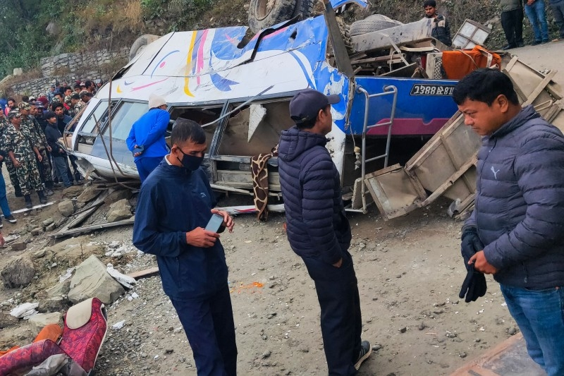 Rescue workers and bystanders gather around the wreckage of a bus following an accident in Sindhupalchowk, some 80 kilometers northeast of the capital Kathmandu, on Sunday. -AFP