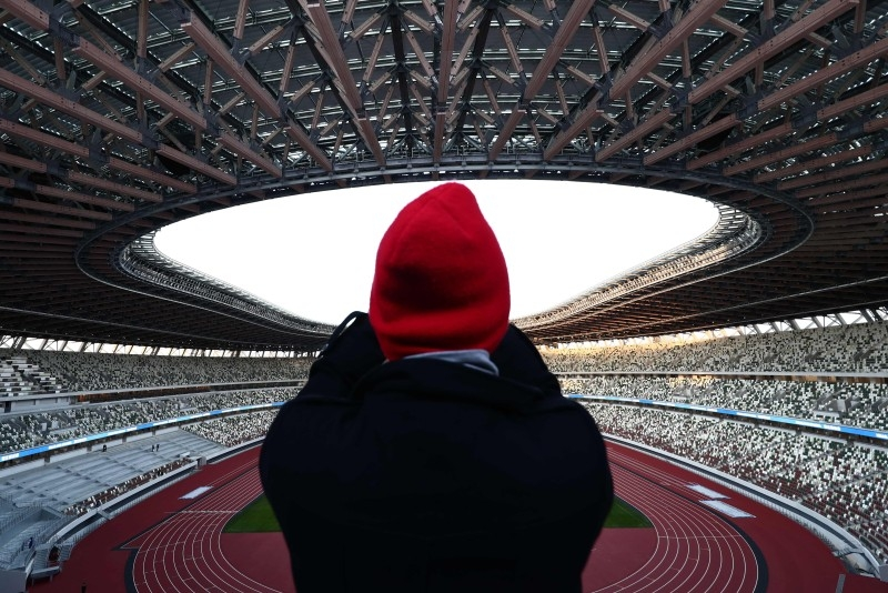 A journalist takes photos at the National Stadium, venue for the upcoming Tokyo 2020 Olympic Games, during a media tour following the stadium's completion in Tokyo on Sunday. Tokyo formally unveiled its 60,000-seater main Olympic Stadium, more than seven months before the 2020 Opening Ceremony — with a host of special features to beat the feared heat. — AFP