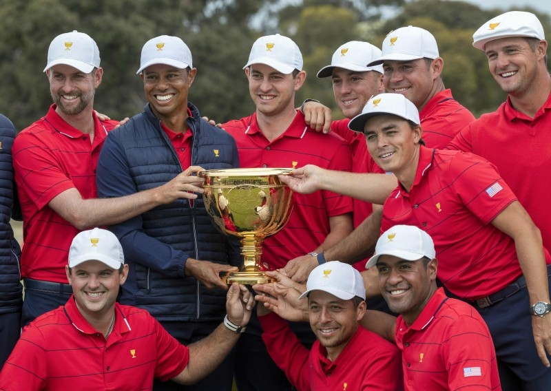 US team captain Tiger Woods (top row, 2nd L) and his teammates pose with the Presidents Cup after their win over the International Team on the final day of the Presidents Cup golf tournament in Melbourne on Sunday. — AFP