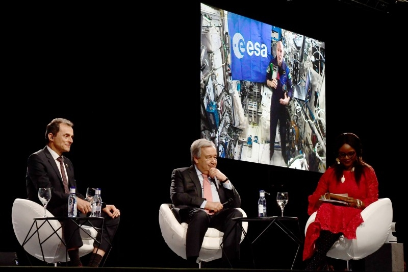 Pedro Duque (L), Spain's caretaker Minister of Science, Innovation and Universities and Antonio Guterres (C), Secretary-General of the United Nations, take part in a conversation with Luca Parmitano (on screen), current international space station commander at the UN Climate Change Conference COP25 at the 'IFEMA - Feria de Madrid' exhibition centre, in Madrid, on Dec. 11. - AFP