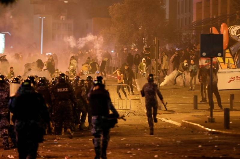 Lebanese riot police clash with anti-government demonstrators (background) in the capital Beirut on Saturday night. — AFP