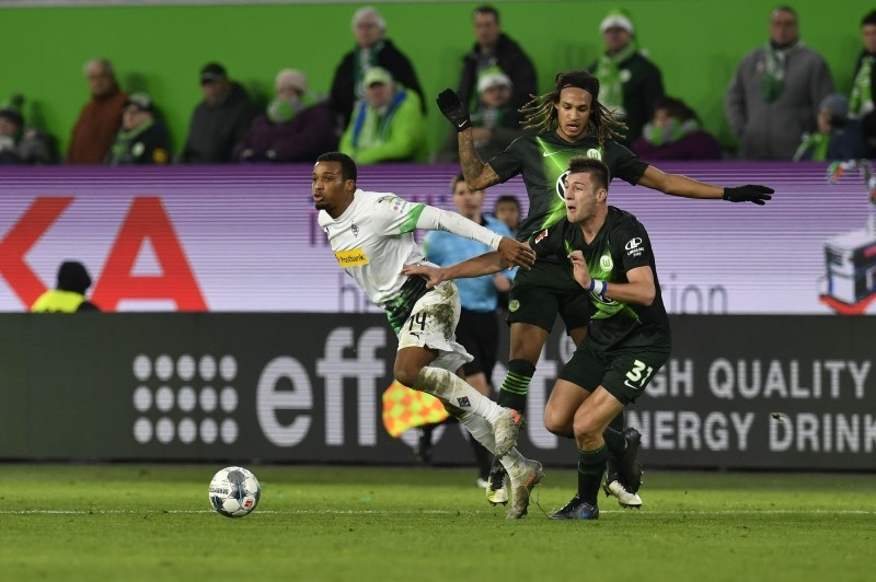 Moenchengladbach's French forward Alassane Plea (L) vies for the ball with Wolfsburg's defenders Robin Knoche (R) and Kevin Mbabu during the German first division Bundesliga football match in Wolfsburg, on Sunday. — AFP