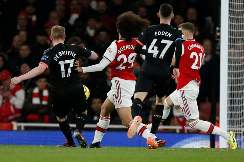 Manchester City's Belgian midfielder Kevin De Bruyne (L) shoots to score their third goal during the English Premier League football match against Arsenal  at the Emirates Stadium in London on Sunday. — AFP