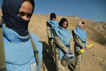 In this photograph taken on November 14, 2019, Afghan deminers working for the Danish Demining Group (DDG) look on during the scanning of a combat zone dating back to the Soviet invasion at Ahangaran in the central afghan province of Bamiyan. -AFP