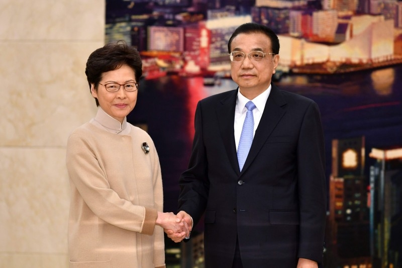 This handout photograph taken and released by the Hong Kong Government on Monday shows Chinese Premier Li Keqiang (R) meeting with Hong Kong Chief Executive Carrie Lam during her annual duty visit, in Hong Kong Hall at the Great Hall of the People in Beijing. -AFP
