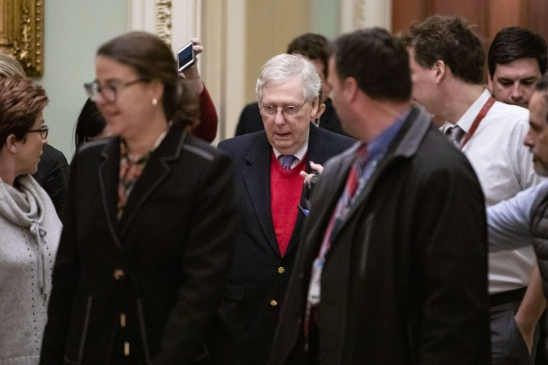 Senate Majority Leader Mitch McConnell (R-KY is surrounded by journalists as he heads to the Senate chambers for a vote  in Washington, DC, on Monday. -AFP