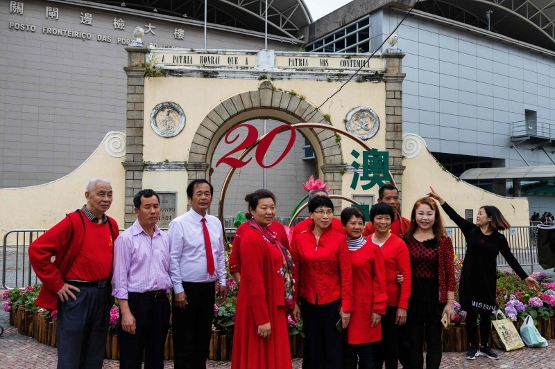 Chinese tourists pose for a photograph in front of Portas do Cerco in Macau on December 15, 2019. -AFP