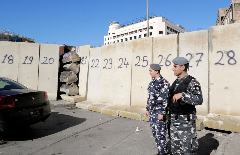 Lebanese policemen stand by concrete barricades that were erected overnight to block or control access to protest sites, following attacks by counter-demonstrators, in the capital Beirut, on Wednesday. — AFP