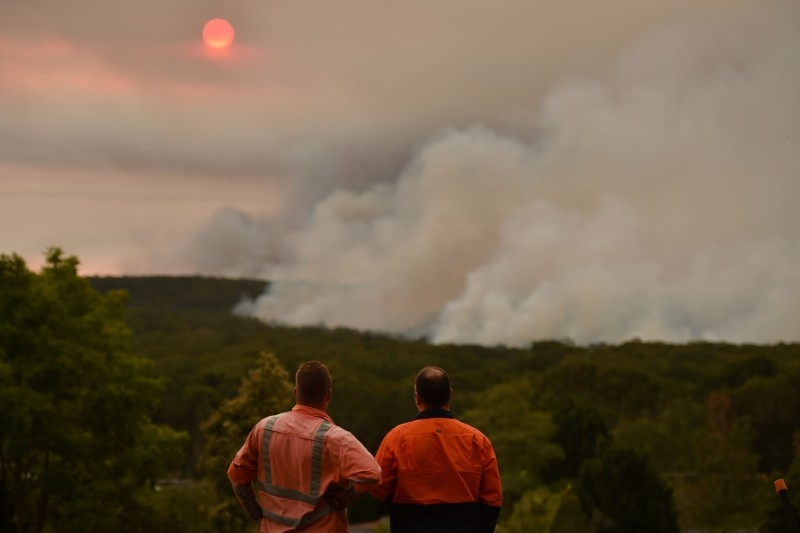 A helicopter drops water onto a large bushfire in Bargo, 150 km southwest of Sydney, on Thursday. — AFP