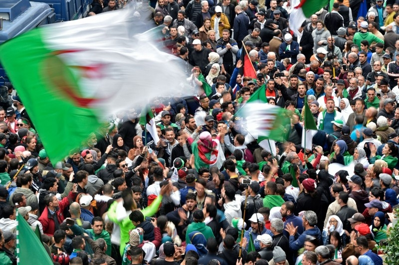Algerian protesters wave national flags during an anti-government demonstration in the capital Algiers on Friday. — AFP