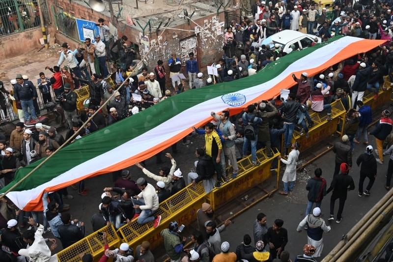 Protesters stand with a large Indian flag by the Jama Masjid mosque at a demonstration against India's new citizenship law in New Delhi on Friday. -AFP