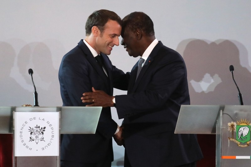French President Emmanuel Macron (L) greets Ivorian counterpart President Alassane Ouattara on the sidelines of a press conference at the Presidential Palace in Abidjan on Saturday, during a three day visit to West Africa. -AFP