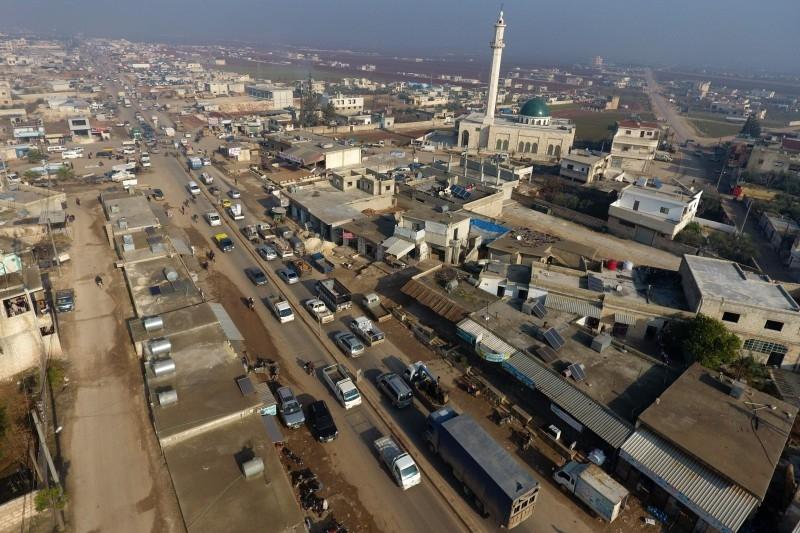 Syrian families flee the village of Hazano, about 20 km northwest of the city of Idlib, toward the Syrian-Turkish border, on Sunday. — AFP