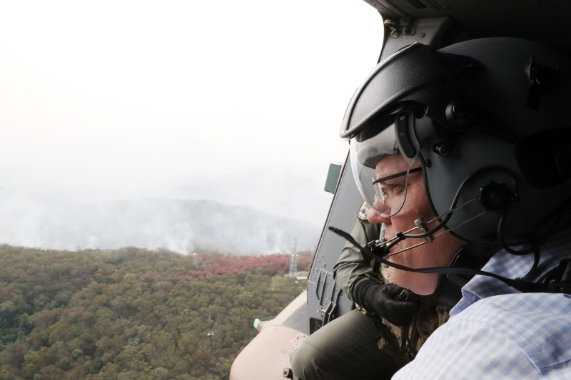 Australia's Prime Minister Scott Morrison, center, flies over bushfires in an Australian Defense Force helicopter in New South Wales on Monday. — AFP