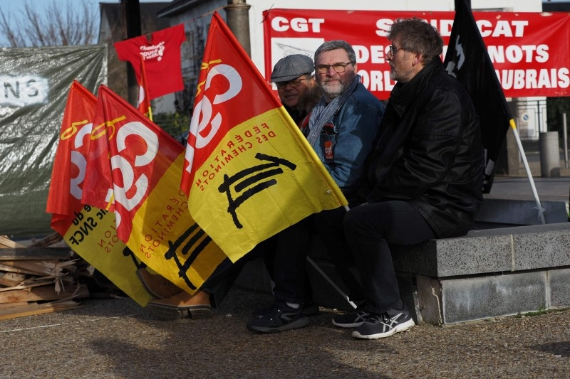 SNCF railway workers gather for their organized Christmas banquet in front of the Les Aubrais station after a meeting against the pension reform on Monday near Orleans, central France. -AFP