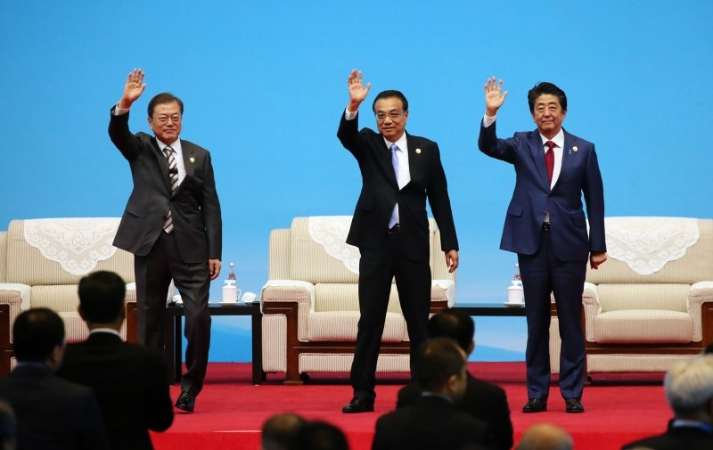 South Korea's President Moon Jae-in (L) shakes hands with Japan's Prime Minister Shinzo Abe during their meeting in Chengdu, southwestern China's Sichuan province on Tuesday. -AFP