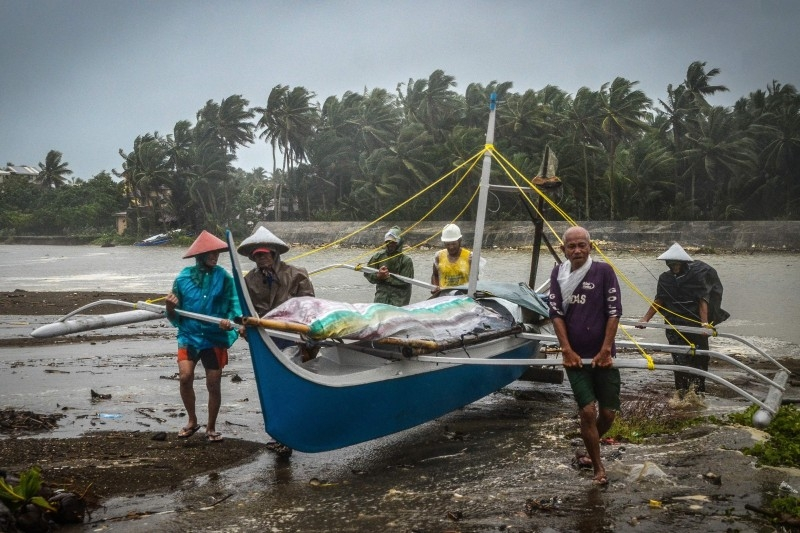 Fishermen carry a boat to higher ground in Baybay, eastern Samar on Tuesday, after typhoon Phanfone hit the central Philippines. — AFP