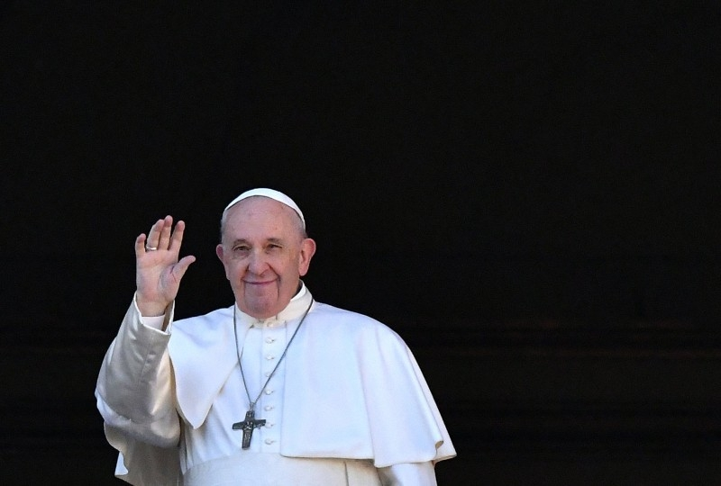 Pope Francis waves from the balcony of St Peter's basilica during the traditional