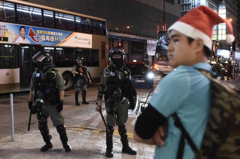 A man with a Santa hat stands in front of riot police during a protest in Mong Kok district in Hong Kong on Wednesday. — AFP