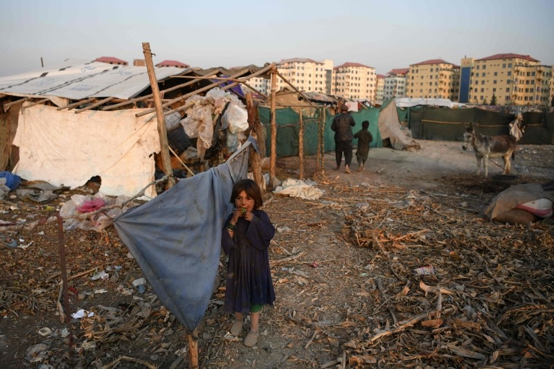 An internally displaced Afghan girl stands outside a temporary home at a refugee camp in Kabul in this Dec. 24, 2019 file photo. — AFP