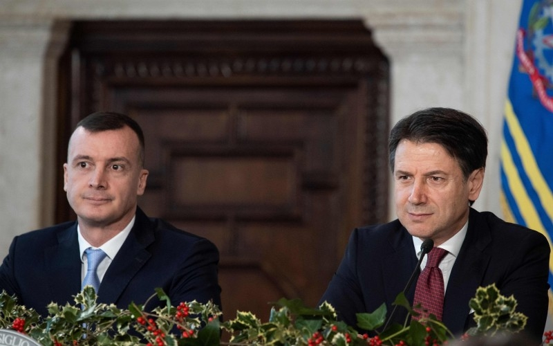 Italy's Prime Minister Giuseppe Conte (R), flanked by his spokesman Rocco Casalino (L), speaks during the end-of-year press conference in Rome, on Saturday. — AFP