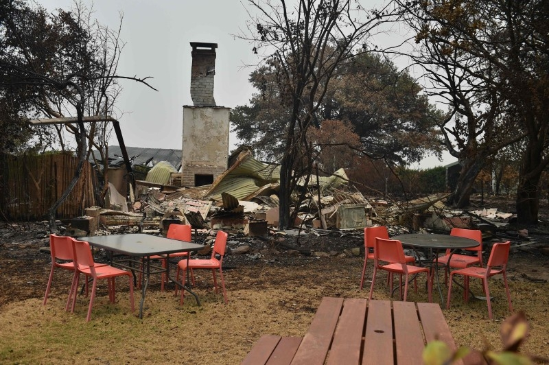 A house and van are seen destroyed after bushfires ravaged the town of Bilpin, 70km west of Sydney  on Saturday. -AFP