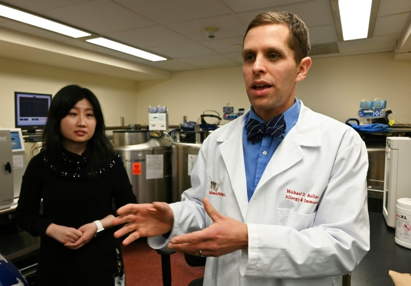 Dr. Michael Keller, an immunologist and Assistant Professor at Children's National Hospital, flanked by Nan Zhang (L), supervisor of the cell therapy lab, explains a new kind of tailored treatment called T-cell therapy during an interview with AFP inside the cell therapy laboratory at Children's National Hospital in Washington, DC on Dec. 12, 2019. — AFP