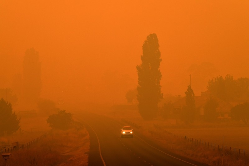 Residents commute on a road through thick smoke from bushfires in Bemboka, in Australia's New South Wales state on Sunday. Australians counted the cost from a day of catastrophic bushfires that caused