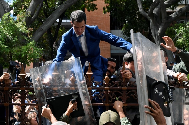 Venezuelan opposition leader and self-proclaimed acting president Juan Guaido is helped to climb a railing in an attempt to reach the National Assembly building in Caracas, on Sunday. -AFP