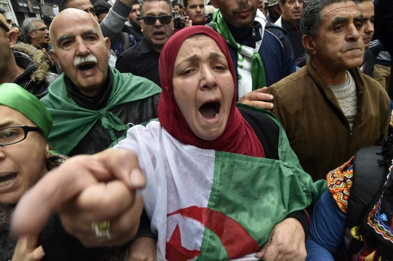 Algerians chant slogans as they take part in an anti-government demonstration in the center of the capital Algiers on Friday. – AFP