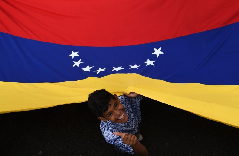 A supporter of Venezuelan opposition leader and self-proclaimed acting president Juan Guaido, gives the thumb up as he holds a Venezuelan national flag during a rally in Caracas, on Saturday. -AFP