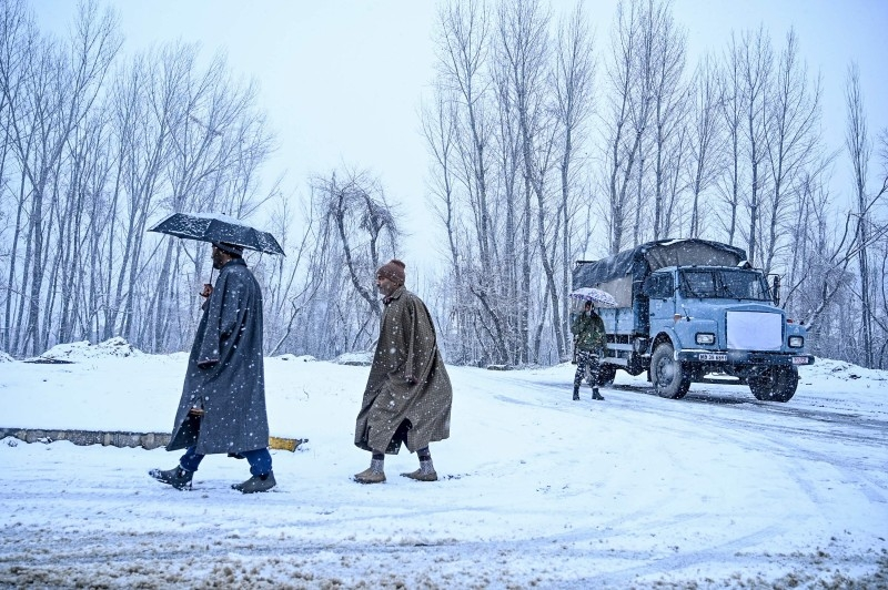 People walk as a security personnel, right, holding an umbrella stands next to a security vehicle near the Dal Lake during a snowfall in Srinagar on Sunday. — AFP