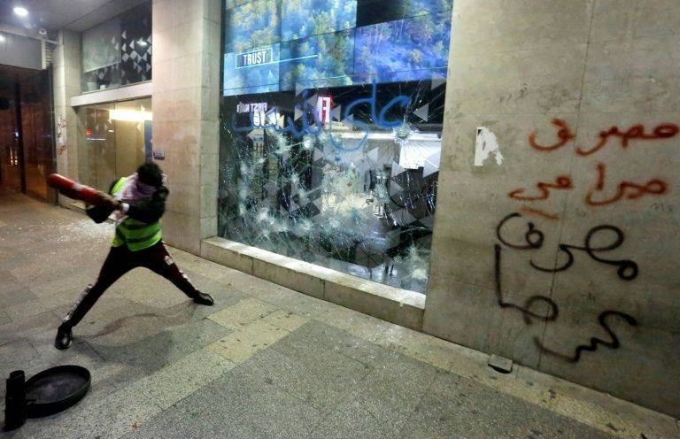 A Lebanese protester smashes the window of a bank in the capital Beirut, as demonstrators demand an end to a months-long political vacuum, with police firing tear gas at the start of a