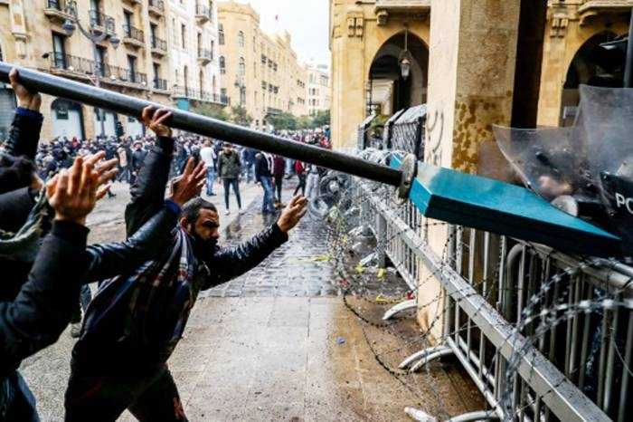 Anti-government protesters use a road sign to taunt security forces taking cover during clashes in the central downtown district in Beirut on Saturday. — AFP
