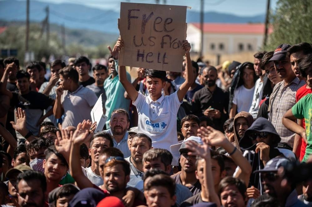 Refugees and migrants take part in a demonstration against their living conditions at the Moria camp on the island of Lesbos, Greece, in this file photo. — AFP