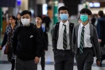 Young students wear face masks in the arrivals hall at Hong Kong's international airport on Wednesday, after China recently confirmed human-to-human transmission in the outbreak of the new SARS-like virus. — AFP