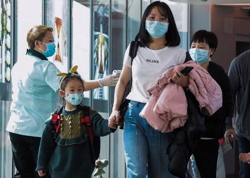 A health officer screens arriving passengers from China at Changi International airport in Singapore on Jan. 22 as authorities increased measure against coronavirus. — AFP