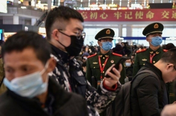 Chinese paramilitary police wearing masks stand guard at a Shanghai train station as the country faces a virus crisis at the start of the Lunar New Year holiday. — AFP