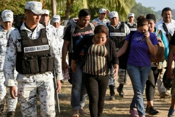 A Central American migrant family is escorted by members of the Mexican National Guard and officers of the Migration Institute after being detained crossing the Suchiate River, in Mexico. — AFP