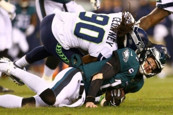 Philadelphia Eagles quarterback Carson Wentz, at bottom taking a helmet-to-helmet hit from Seattle's Jadeveon Clowney in a playoff game, was among the NFL players who reported himself to concussion protocol in the 2019 campaign. — AFP