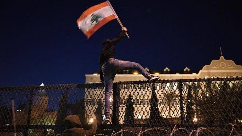 Protesters attack barriers in front of the Grand Serail, the prime minister's headquarters, in Beirut. — Courtesy photo