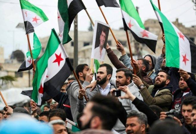 Syrian protesters wave the three-star flag of the opposition in Maaret Al-Numan on March 15, 2019. — AFP file photo