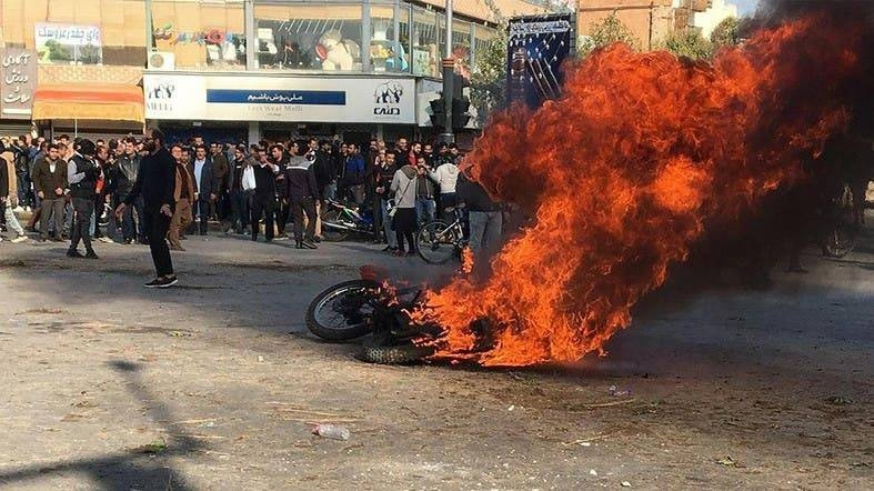 Iranian protesters gather around a burning motorcycle during a demonstration against an increase in gasoline prices in the central city of Isfahan, in last November. — AFP